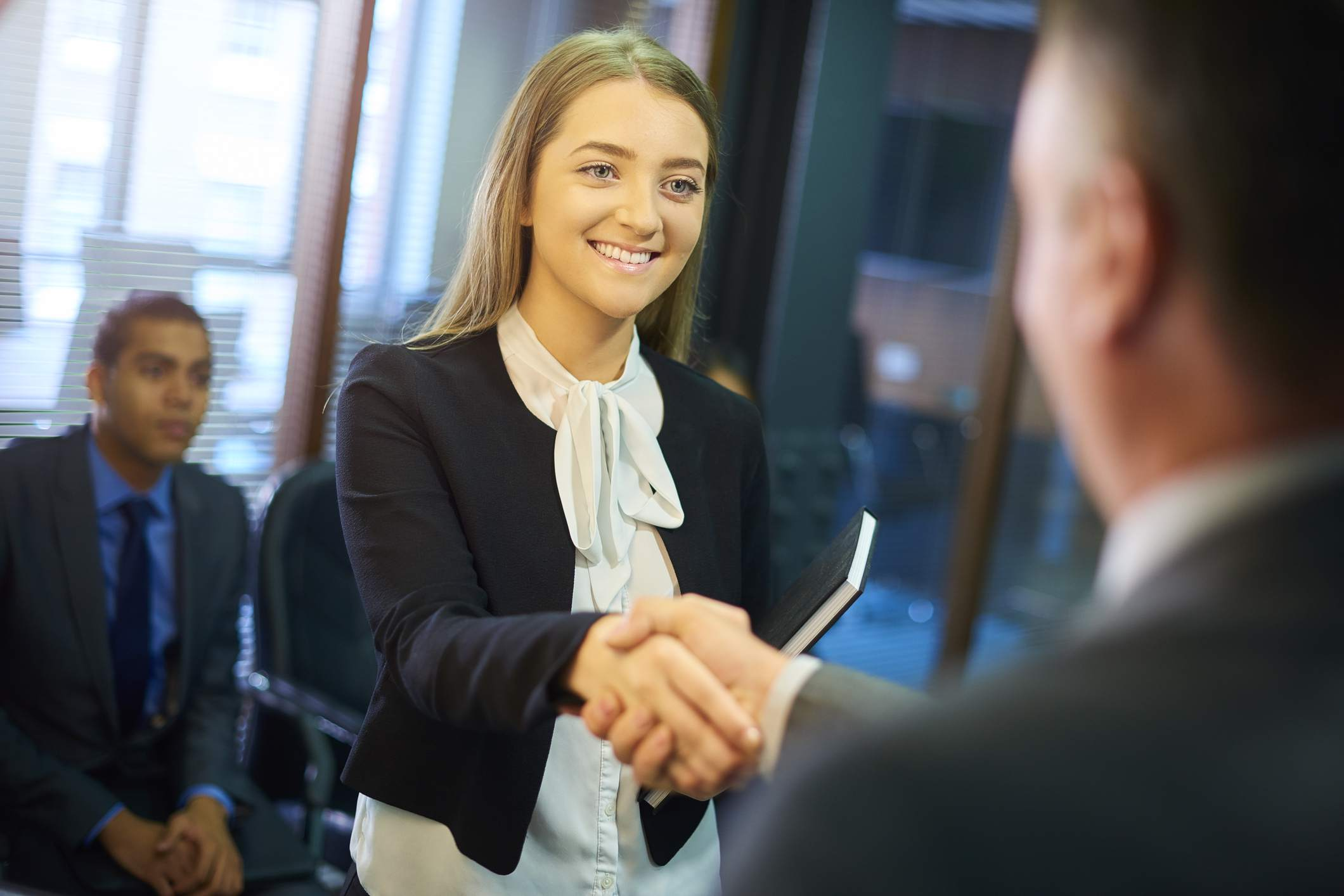 Young woman shaking hands with employer