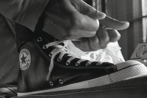 Hands tying the Converse sneaker in