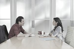 Meeting at table in conference room, side view
