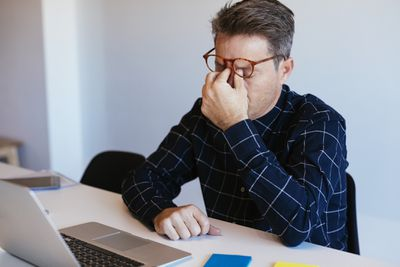 Businessman at desk in office rubbing his eyes - stock photo