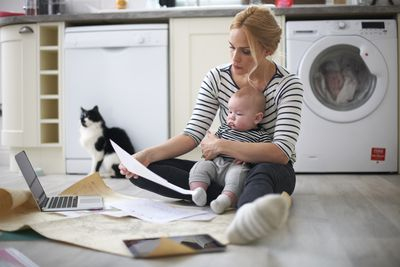 Woman holding baby son in arms, looking through work on kitchen floor, laptop and digital tablet in front of her