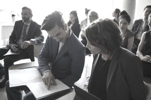 Businessman and businesswoman reviewing paperwork in conference audience