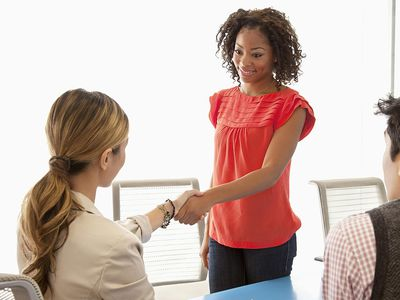 A salesperson closing a deal, shaking hands and using direct eye contact with the customer.