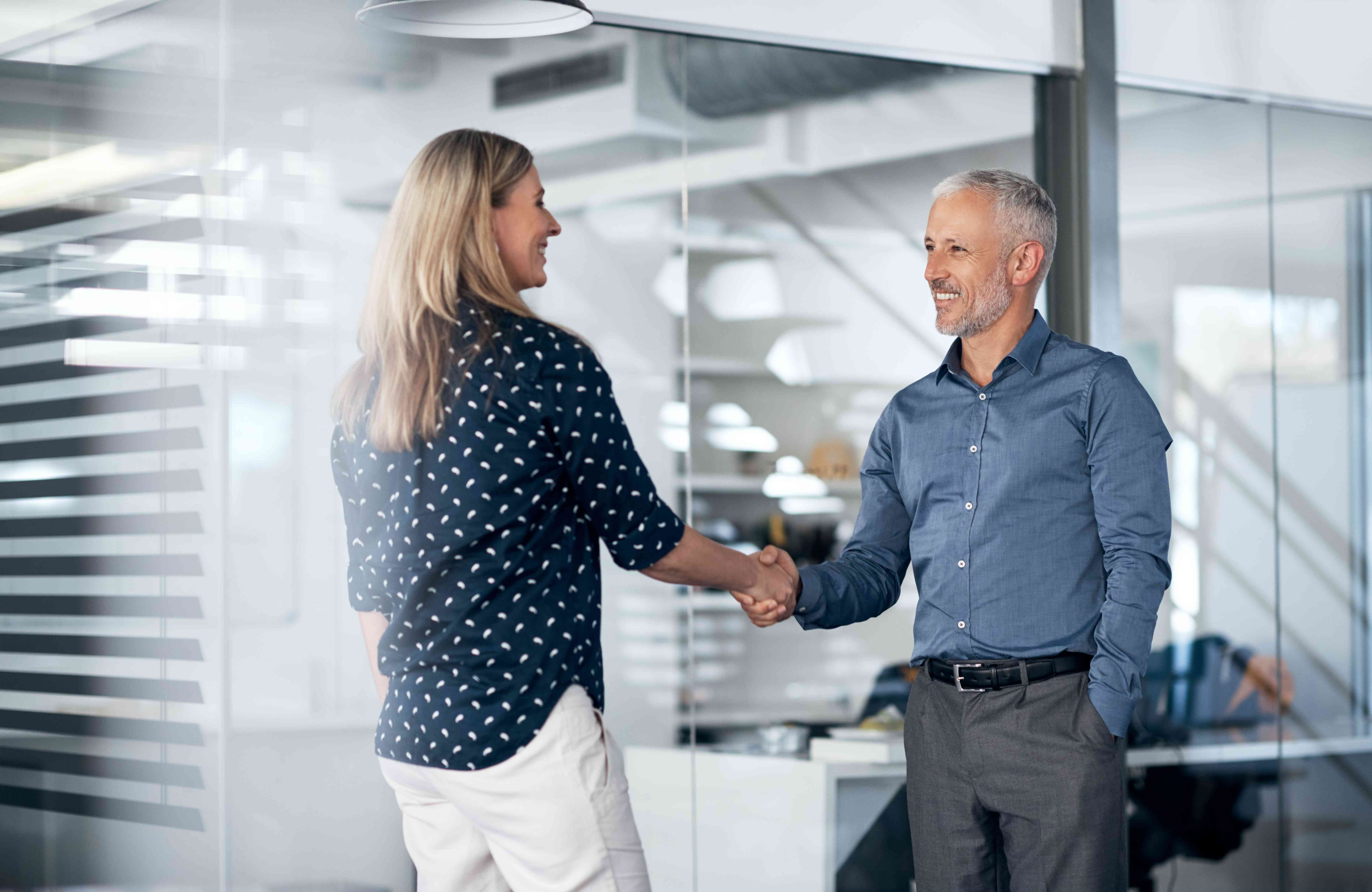 Man and woman shaking hands in a business office.