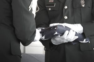 army officers folding flag at military funeral