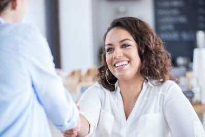 Young woman greets colleague in coffee shop