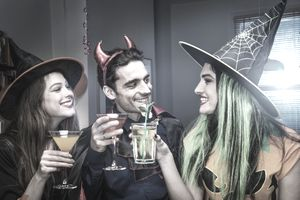 Halloween witches and devil toasting cocktails.