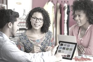Two women working with a designer