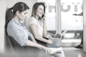 Laughing woman on cell phone in office waiting area