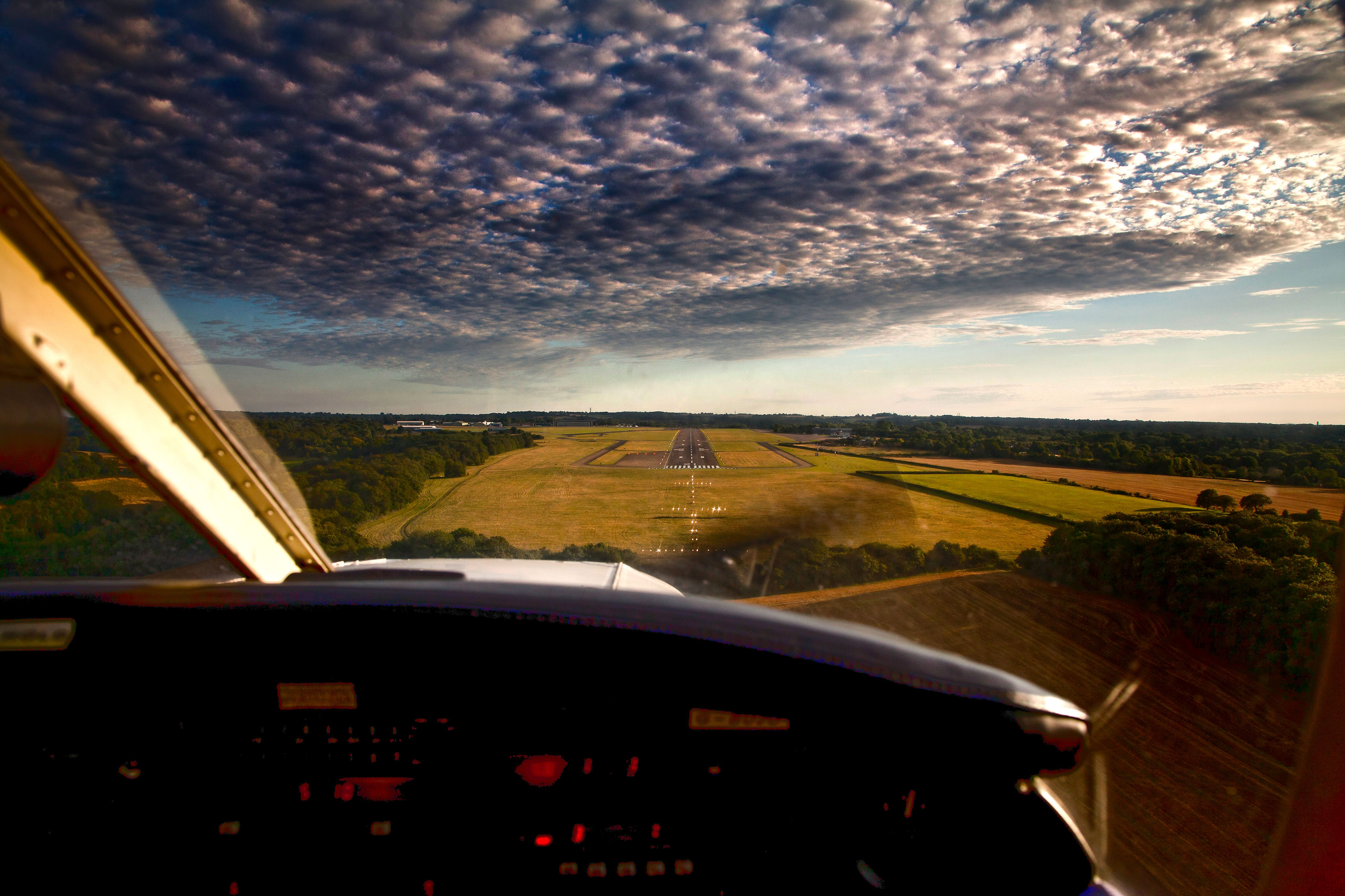 View from the cockpit of a plane flying over the English countryside.