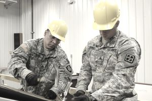 Two Army carpentry and masonry specialists in fatigues and hardhats apply roof covering
