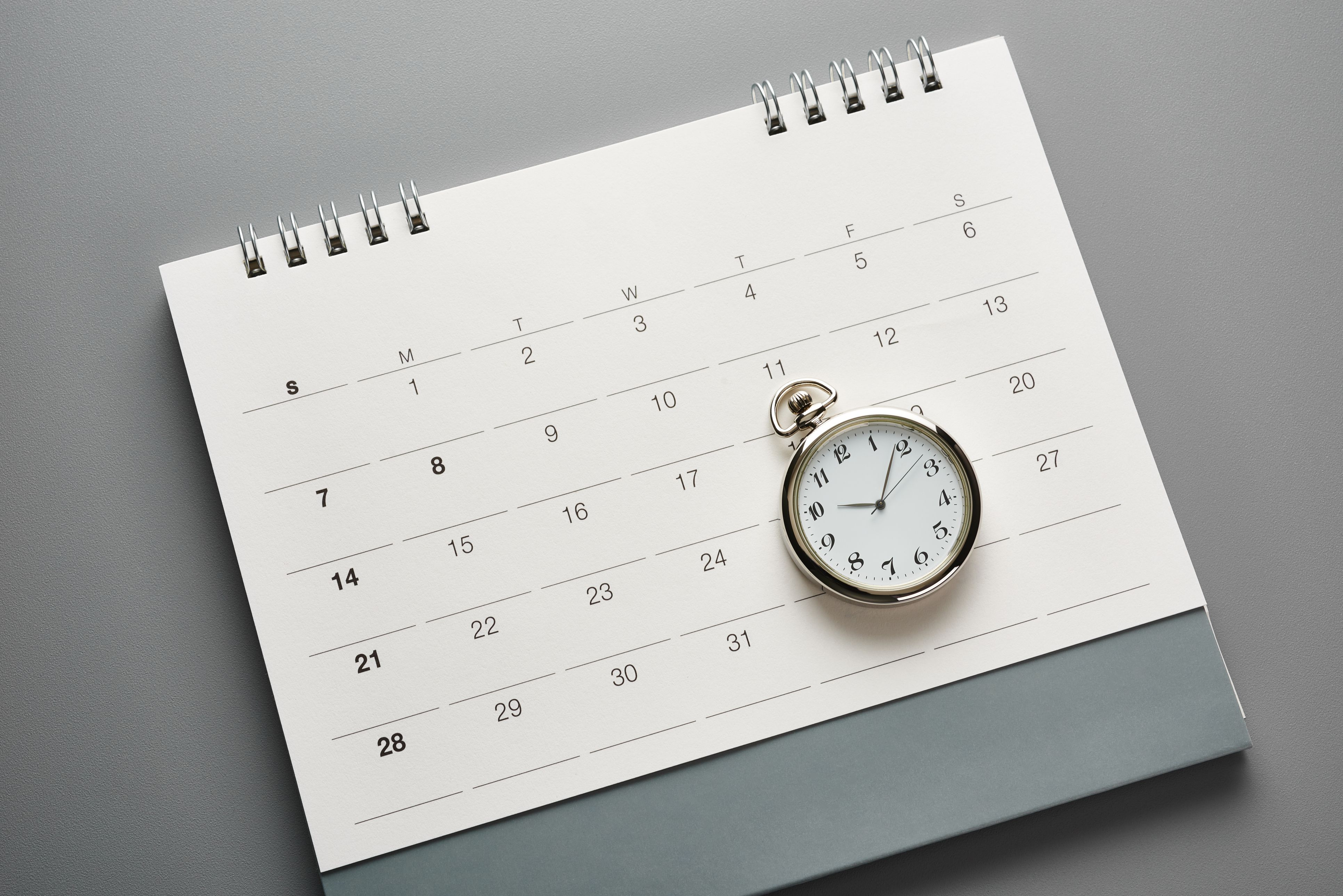 Pocket watch laying on top of a calendar, representing deadlines.