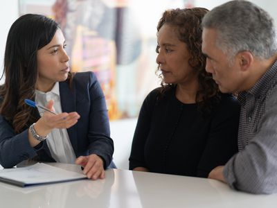 A senior couple is working with a consultative salesperson.