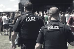 Rear view of a pair of police officers at a park during a festival.
