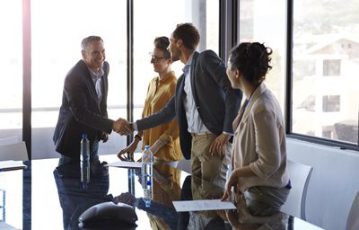 Salespeople shake hands after closing a deal.