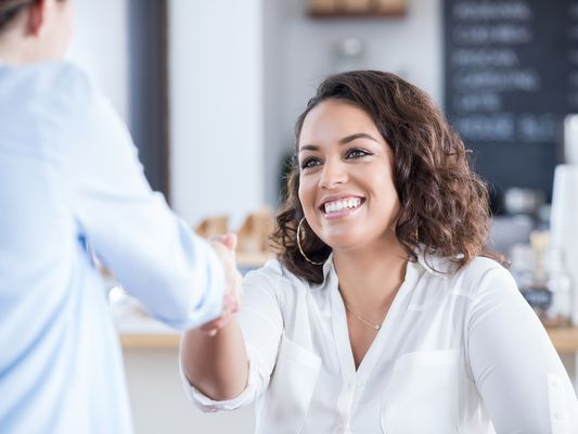a businesswoman greets interviewee in coffee shop