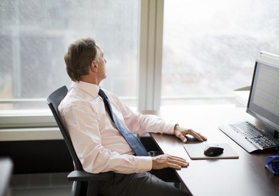 Businessman gazing out window in office