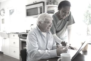 Female home nurse helping senior male patient reordering prescription medication at laptop