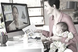 Mother holding daughter and working from home