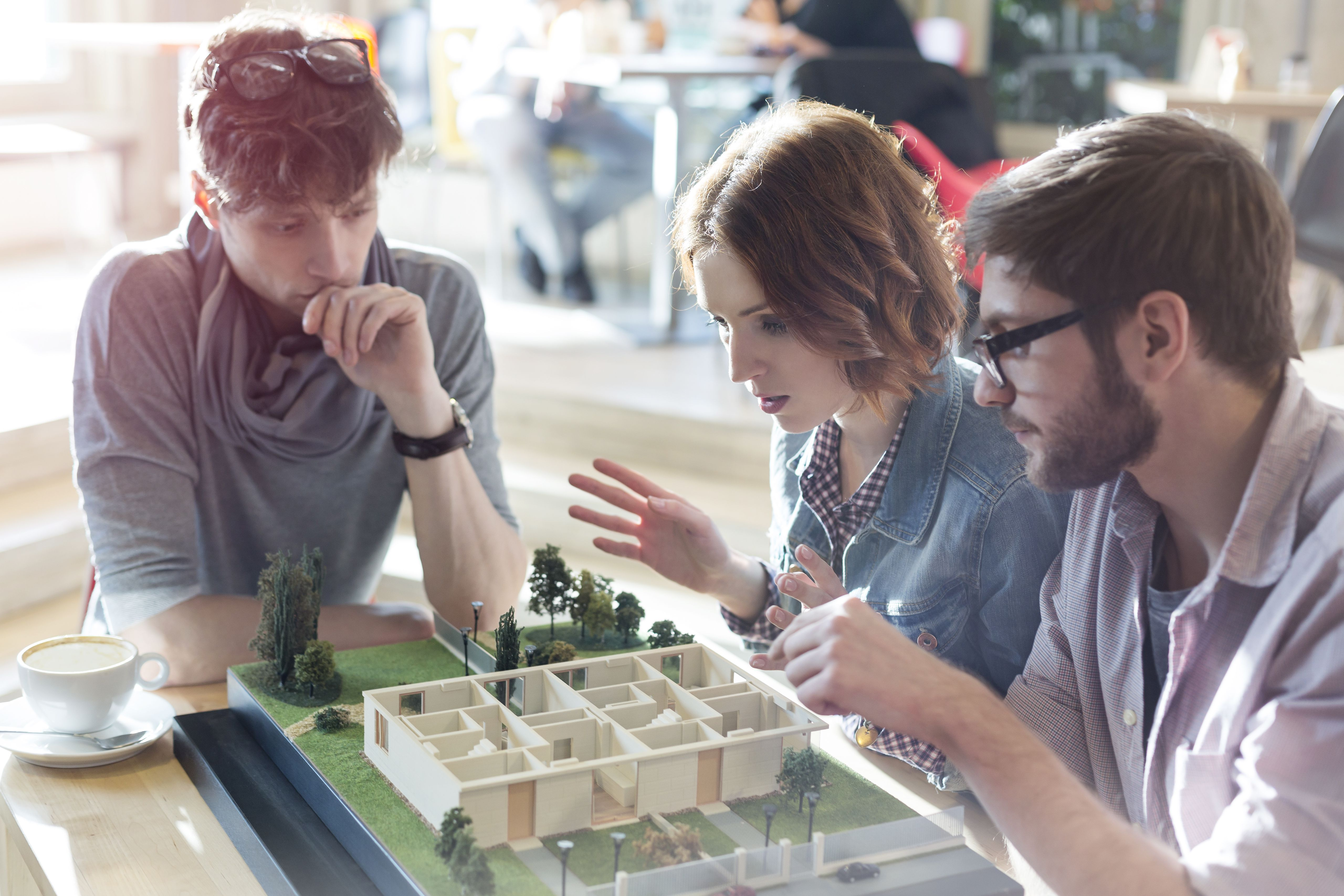 Architecture students brainstorming at building model in classroom