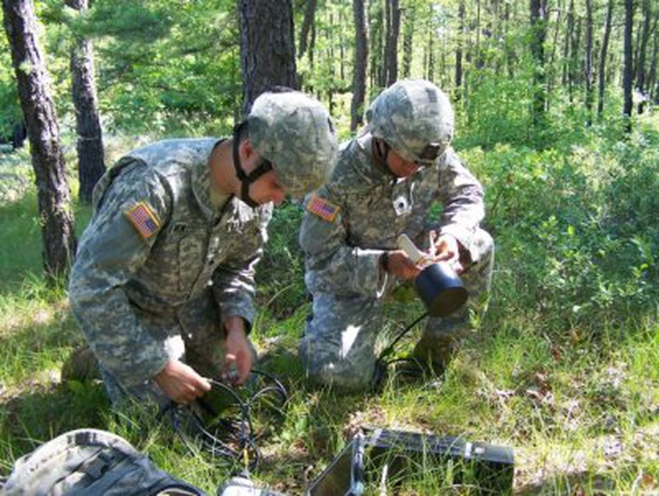 Two Soldiers set up a One System Remote Video Terminal as they prepare to begin an exercise at Fort Dix, N.J.