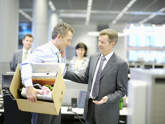 businessman leaving office with box of personal items being consoled by coworker or boss