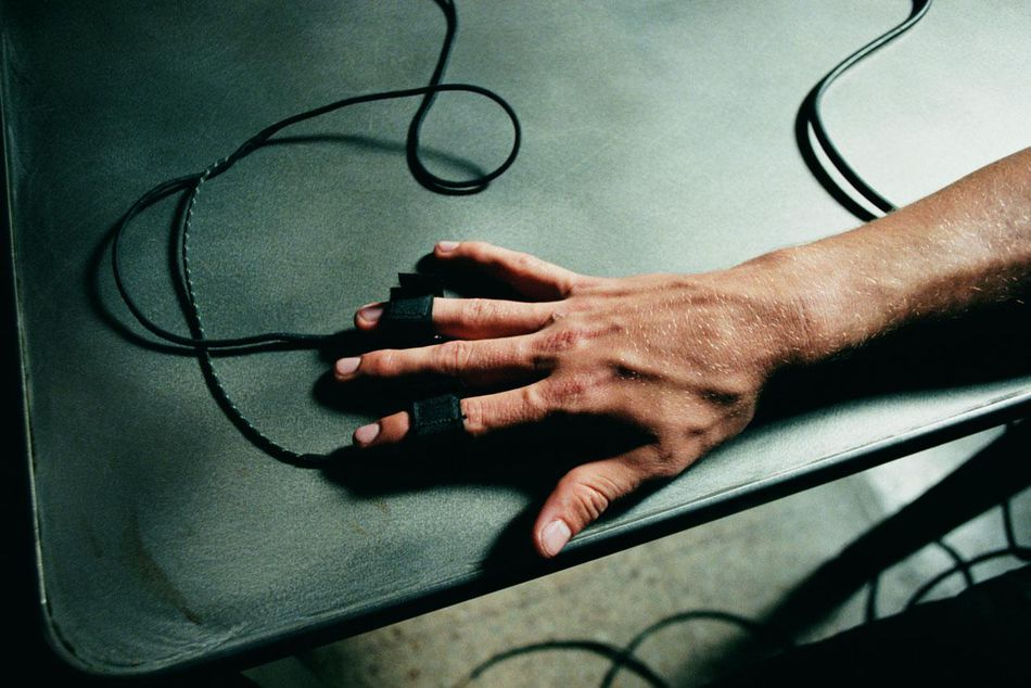 Hand hooked on a table with feed for a lie detector test attached to two fingers.
