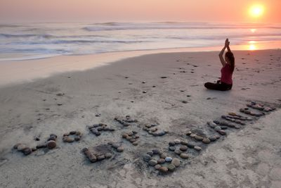 A woman practicing yoga on the beach as part of work-life balance