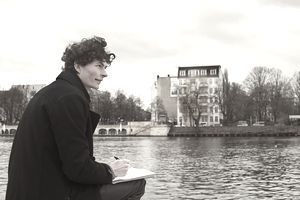 Man writing in a journal by the river