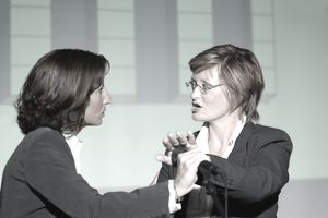 2 women in a heated discussion where on block the microphone the other is holding