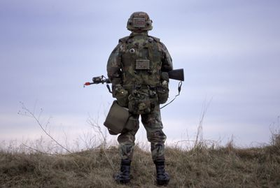 A rear view of a soldier patrolling with a gun in his hands, New York, USA.