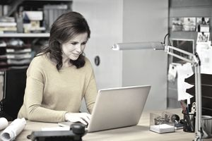 Woman composing a resignation letter on computer
