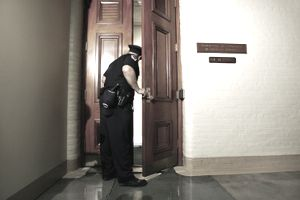 Law enforcement officer opening the door to the Committee on Standards of Official Conduct. meeting.