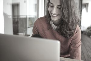 Smiling young woman using laptop on balcony
