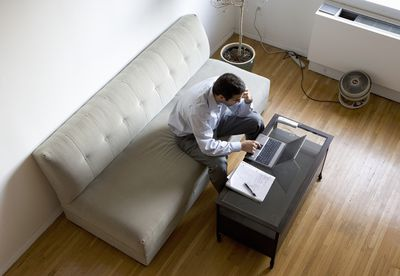 Young man sitting on sofa using laptop on coffee table, elevated view