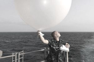 U.S. Navy Aerographer's Mate standing on the fantail of a ship releasing a weather balloon.