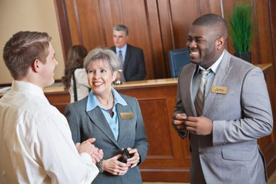 Hotel management discussing something with guest in the lobby