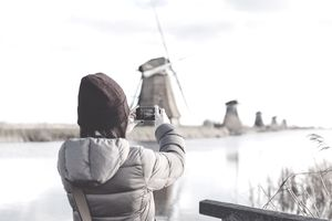 Girl traveling abroad, taking picture of windmills with smartphone