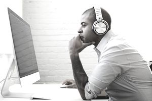 Male music agent sitting on computer with headphones reviewing a show he booked