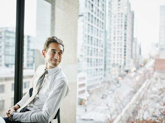 Smiling businessman seated in office with panoramic view of city