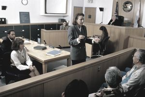 Lawyer speaking to jury in a courtroom setting.