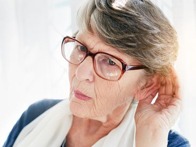 older woman with hand cupped to ear listening
