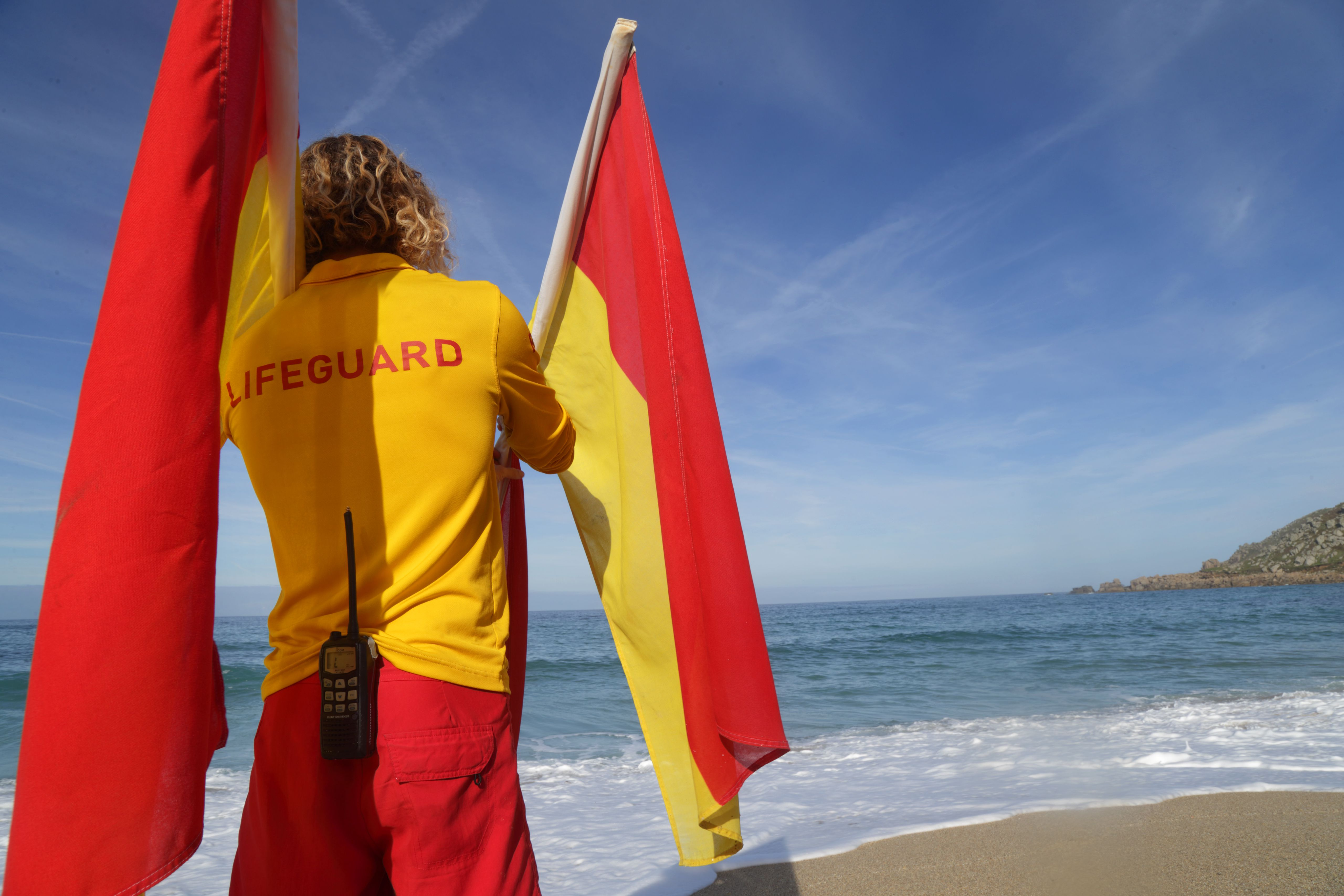 Lifeguard on beach with flags