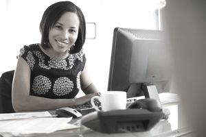 Portrait of smiling mixed race businesswoman at computer