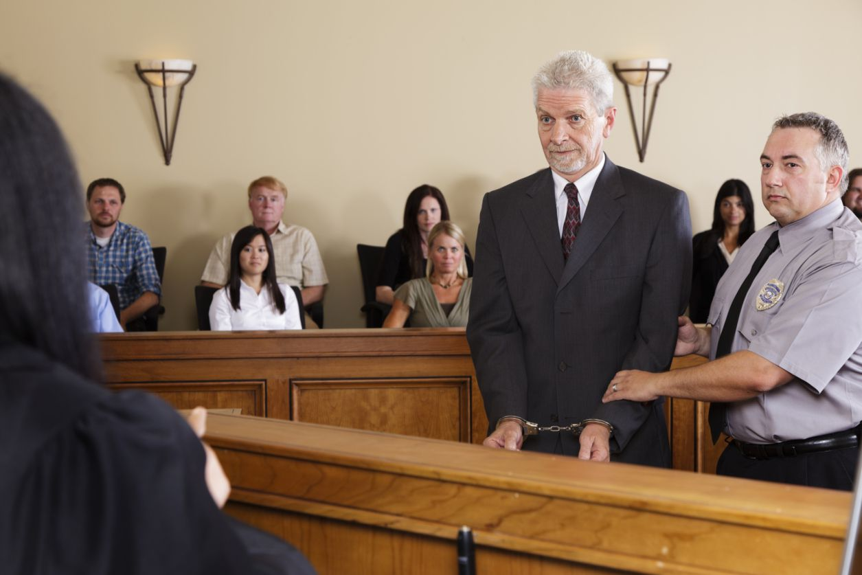 A court bailiff presents a defendant in custody to a judge with jury sitting in background.