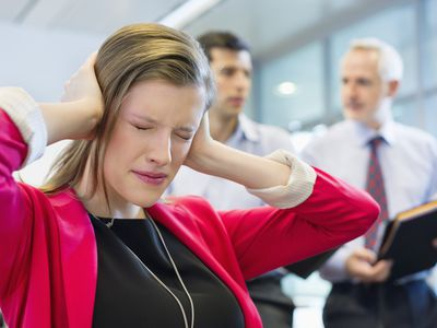 Frustrated worker covers their ears as bosses argue