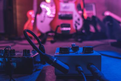 Close-up of guitar effects pedals set up on a stage.