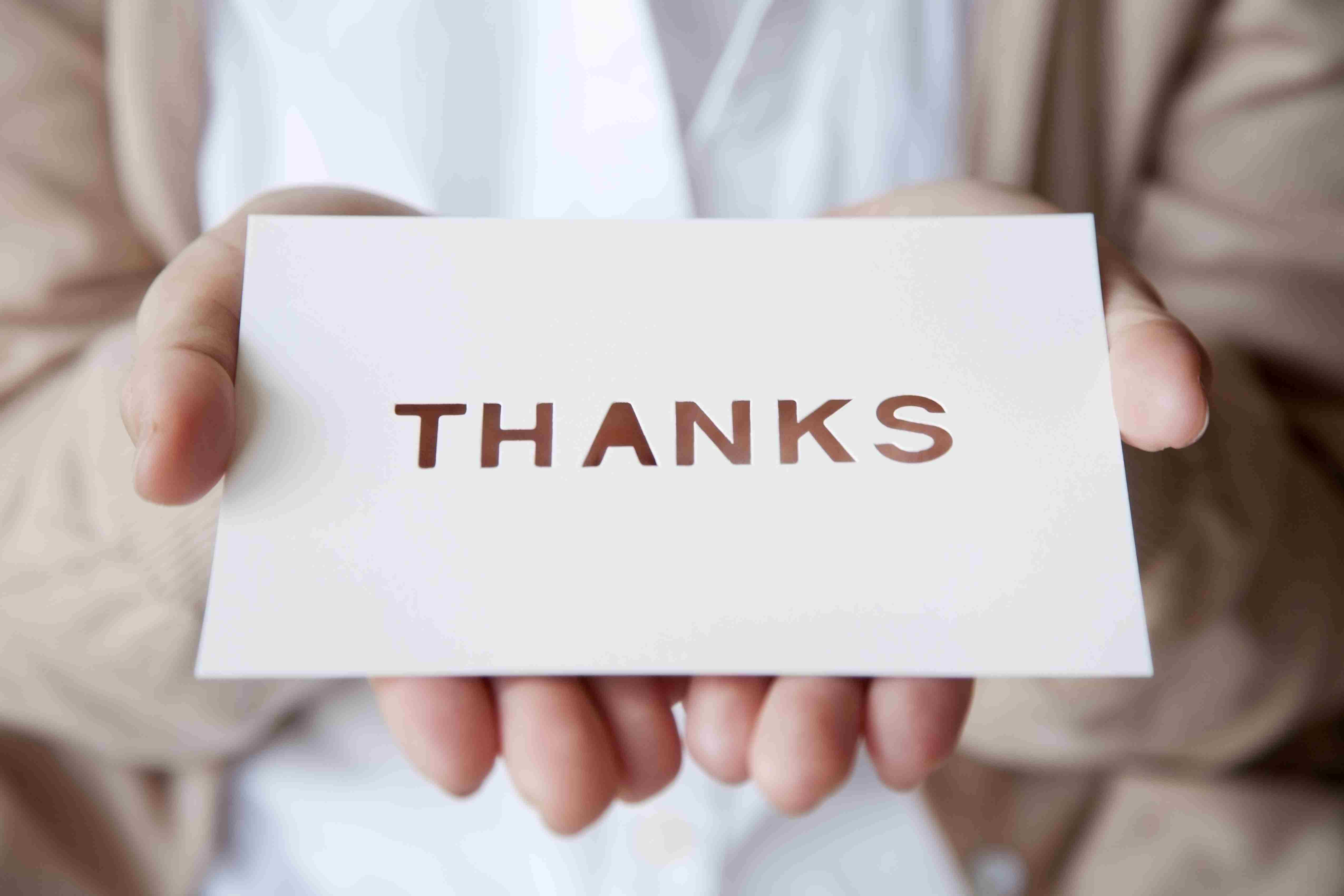 Closeup of hands holding out a thank-you card