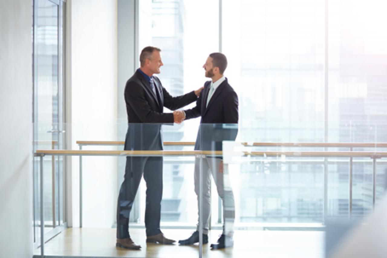 Two businessmen shaking hands after one of them has resigned from his job on good terms.
