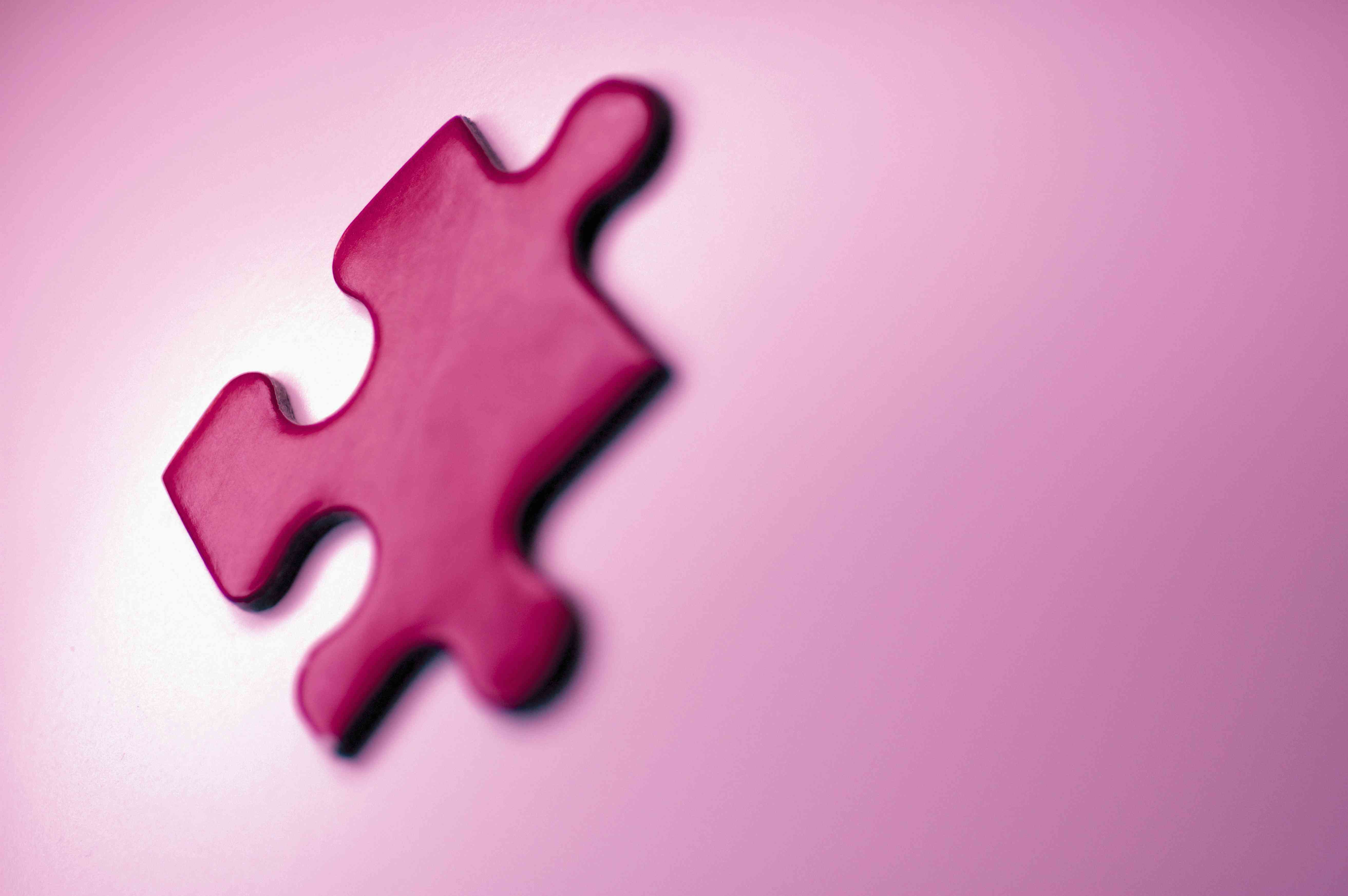 Puzzle piece on pink background